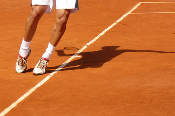 Athletic pose of a tennis player serving showing only feet