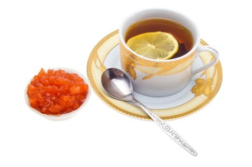a cup of tea with lemon and jam in a bowl