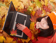 Girl in autumn orange foliage with laptop. Outdoor.