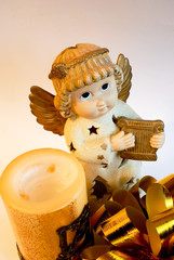 christmas angel with gold wings and harp, candle and bow