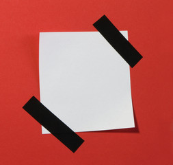 Post-it note isolated on red background.