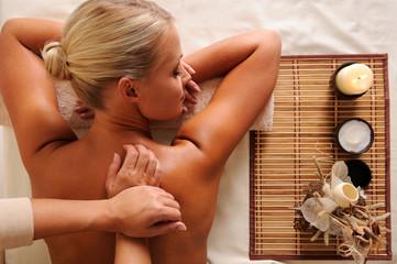 massaging  back of a beautiful young caucasian female