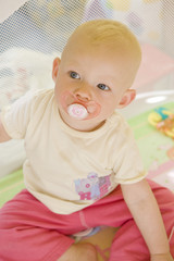 portrait of toddler with pacifier sitting in cot
