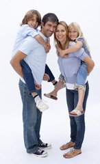 Family giving children piggyback ride against white