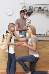 Mother giving girl the school lunch in the kitchen
