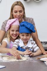 Mother helping her children baking