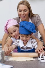 Mother and children baking biscuits in kitchen