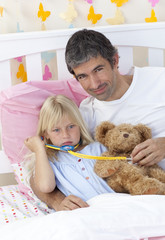 Sick girl playing with a stethoscope with her father