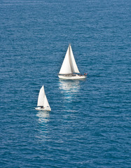Two White Sailboats on Dark Blue Water