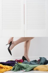 woman removes high heels in fitting room