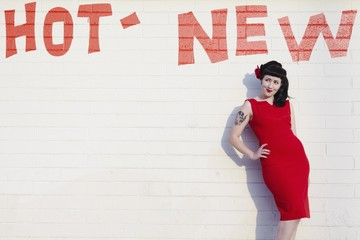 Retro woman in red dress posing against a brick wall