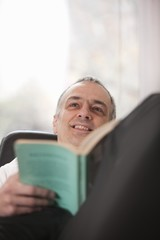 Mid adult man relaxing at home reading a book