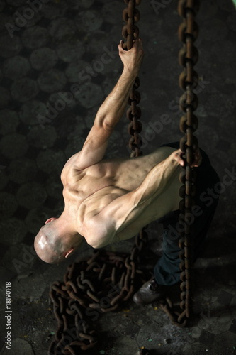 Muscular man  leaning over and pulling on chains.