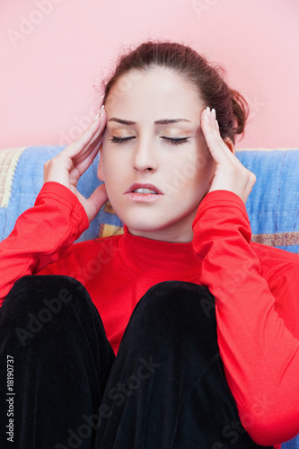 Young woman having headache at home