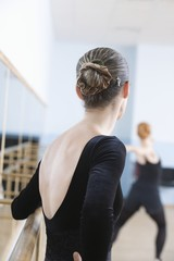 Young woman stands at barre in ballet rehearsal room