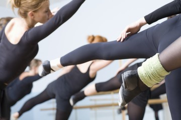 Young women stretch into ballet positions