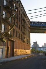 warehouse exterior with fire exit and new york bridge