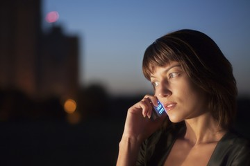 Woman talks on mobile phone at night