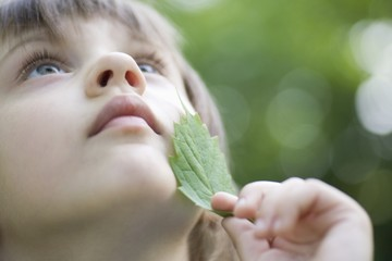 Girl holds leaf to her chin looking up