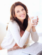 Portrait of woman holding coffee cup by laptop