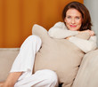Portrait of happy woman sitting with pillow on couch