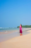 pleasant woman walking at the beach poster