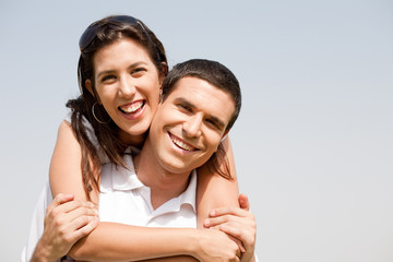 Happy young guy piggybacking his girlfriend