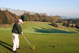 Senior golfer teeing off in autumn