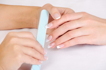 Manicurist   polishing female fingernails