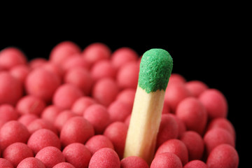 Single green matchstick among red ones, out of the crowd concept