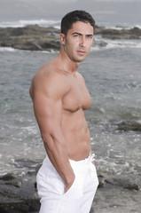 beautiful man near the sea without shirt .