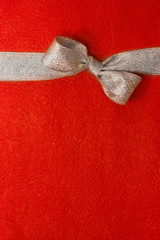 silver gift ribbon and bow on red background. some other you may