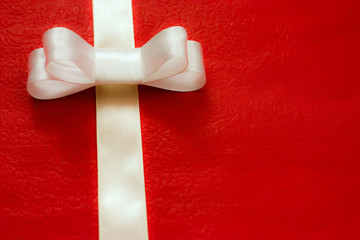 white gift ribbon and bow on red background. some other you may