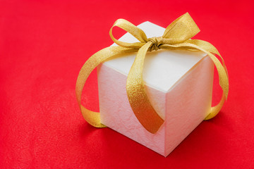 white gift box with a golden ribbon and bow on red background
