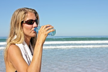 Young fit woman drinking water