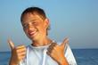 smiling teenager boy against sea shows gesture îê two hands