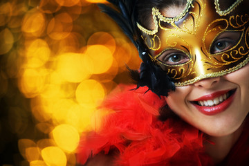 Beautiful young woman in carnival mask over gold background
