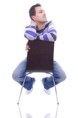The thoughtful young man on a chair, isolated on white backgroun