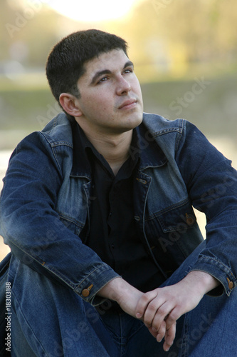 Young man sitting and looking aside with a thoughtful look
