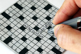 Solving the cross word puzzle from the newspaper poster