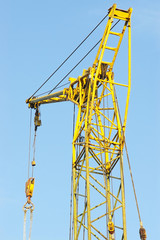 Part of yellow construction crane against blue sky