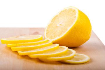 The lemon cut by segments lies on chopping board.