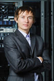 Young businessman in hi-tech datacenter in front of equipment poster