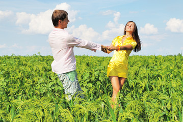 Young couple playing on field in sunny day