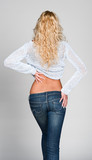 Back view of young female in sweater and jeans isolated