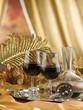 calici di vino rosso su vassoio argentato con  ambientazione oro