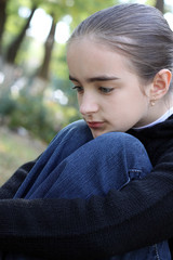 Portrait the sad girl of the teenager in a jacket and jeans.
