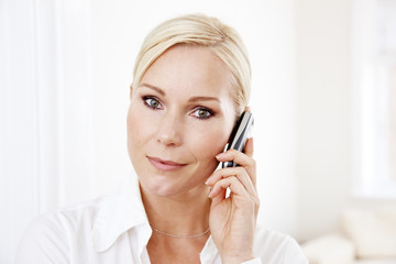 Blond businesswoman on white with mobile