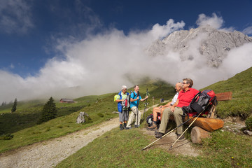 senior hikers at short break on bench in beautiful mountains