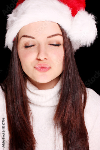 Girl blowing kiss in christmas hat